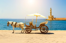 Carriage With White Horse On Waterfront Of Chania Crete Greece, Bright Sunny Day On The Background Of The Ancient Lighthouse And The Sea