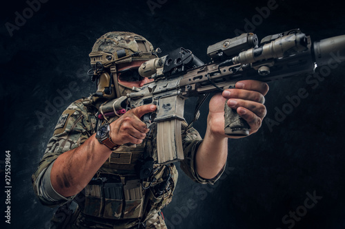Fotomural  Military man in full equipment with wach on his hand is holding machine gun while posing for photographer over dark background