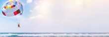 Parasailing Water Amusement - Flying On A Parachute Behind A Boat On A Summer Holiday By The Sea In The Resort. Space For Text. Panoramic View
