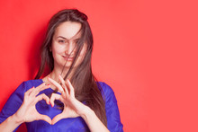 Concept: Love Is Blind. Portrait Of Pretty Romantic Young Woman Making A Heart Gesture With Her Fingers Against Red Background. Free Space For Text And Design.