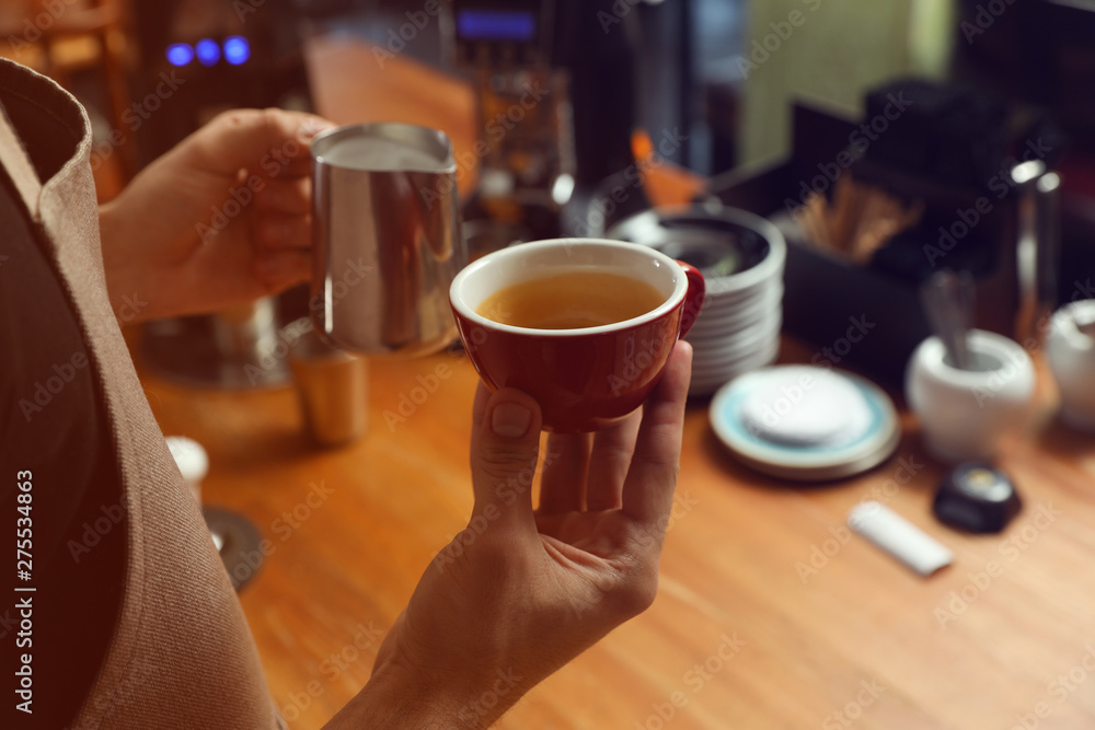 Fototapety, obrazy: Barista holding cup of coffee and jug with milk at bar counter, closeup. Space for text