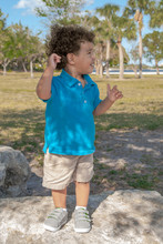 A Toddler Stands Upon A Large Rock At The Park And Looks To His Left. The Summer Sun Dapples Through The Trees Provides Some Shade For The Little Boy With His Hand Up For Balance.