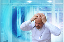 Elderly Bald Doctor With A Phonendoscope Around His Neck In Despair Clutched His Head With His Hands In A Blue Vortex