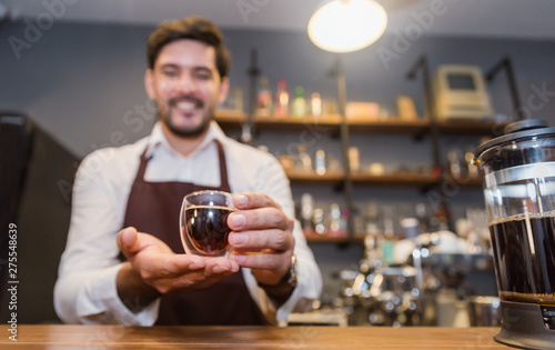 Tuinposter Bar Startup successful small business owner handsome man hand holding espresso cup in coffee shop. Portrait of young caucasian man barista cafe owner. Entrepreneur business concept