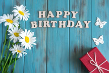Happy Birthday Inscription. Natural Daisies On A Wooden Background With The Inscription Happy Birthday. Greeting Card Design. Floral Background. Flat Lay, Top View.