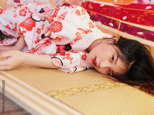 Fotografia Portrait of attractive Chinese woman wearing traditional Japanese Kimono, lying on the tatami mats and looking at camera, oriental beauty