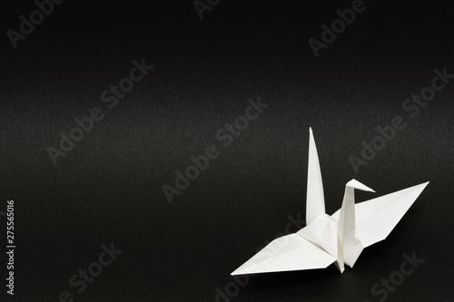 Fototapeta white origami paper crane on black background