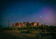 The Desert Wilderness East Of Phoenix, Arizona Photographed Under Clear Starry Desert Skies That Seem To Glow With Color. Desert Plants And Saguaro Cactus Grow Around The Superstition Mountains