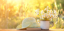 Beautiful Composition With Chamomile Flowers In Cup, Old Book, Braided Hat In Summer Garden. Rural Landscape Natural Background With Chamomile In Sunlight. Summertime Season. Copy Space