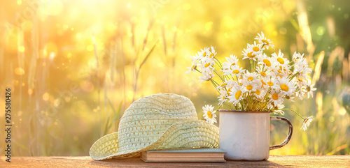 Foto auf Leinwand Gelb Schwefelsäure beautiful composition with chamomile flowers in Cup, old book, braided hat in summer garden. Rural landscape natural background with Chamomile in sunlight. Summertime season. copy space