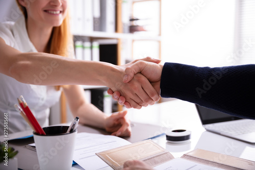 Poster de jardin Route Businesswoman Shaking Hand With Her Colleague Over Desk