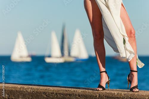 Fotografiet Woman feet in high heels shoes on sea pier