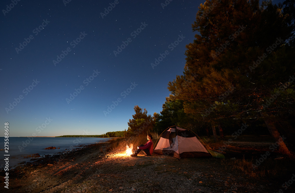 Fototapeta Night camping at sea shore. Attractive tourist girl sitting relaxed in front of tent at campfire under bright starry sky, enjoying beautiful view of clear blue water. Tourism, active lifestyle concept - obraz na płótnie