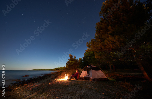 Fototapeta Night camping at sea shore. Attractive tourist girl sitting relaxed in front of tent at campfire under bright starry sky, enjoying beautiful view of clear blue water. Tourism, active lifestyle concept obraz na płótnie