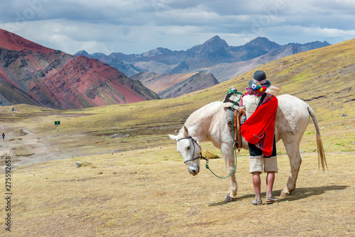 Photo Man dressed in traditional clothing with a horse in Rainbow Mountain, near Cusco