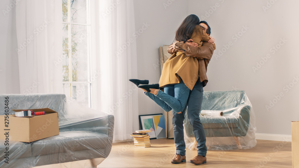 Fototapeta Happy and Excited Young Couple Look Around In Wonder at their Newly Purchased / Rented Apartment. Girl Jumps Into His Boyfriend's Arms Hug. Big Bright Modern Home with Cardboard Boxes Ready to Unpack.