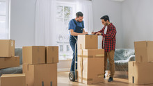 Happy New Homeowner Welcomes Professional Mover With Hand Truck Full Of Cardboard Boxes, Receives His Goods And Signs On Clipboard.
