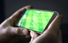 Watching Football And Sport Stream With Mobile Phone. Man Streaming Soccer Game Live, Video Replay Or Highlights Online With Smart Device. Sports Fan And Program Of Tv Network In Smartphone Screen.