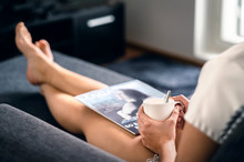 Sunday Morning With Magazine And Coffee. Happy Millennial Woman Relaxing With Fashion And Beauty Trends News And Cup Of Tea. Lady Enjoying Day Off And Me Time On Comfy Couch. Fun Weekend Freetime.