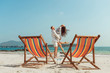 Romantic holiday travel. Portrait of happy young couple hugging near with deck chairs in luxury beach hotel at sunset near sea. Love and relationship concept. Summer vacation