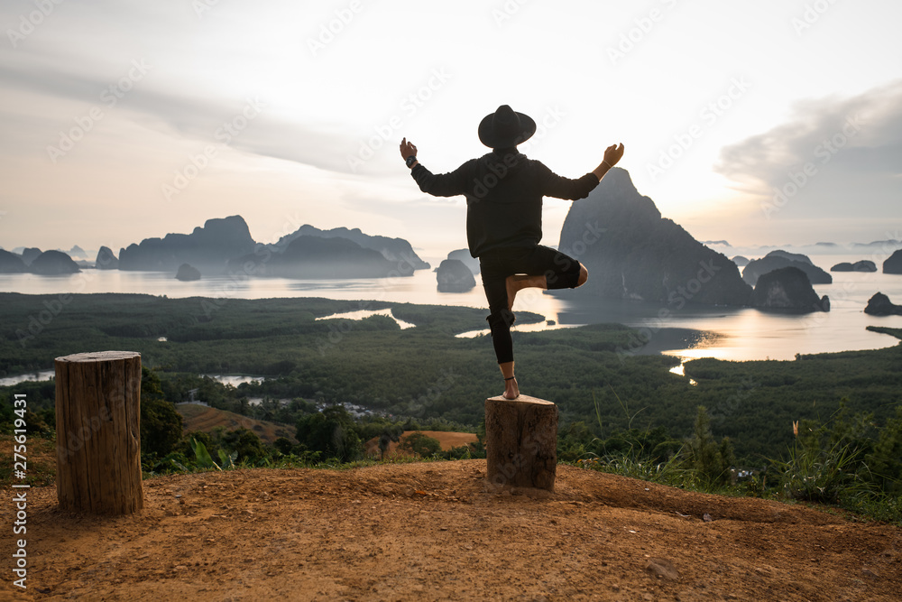 Fototapeta Back view of a Yoga pose. Happy man in black clothes doing yoga pose standing on the tree. Incredible sunset background with mountains and lakes. The concept of balance and harmony in life. Boho style