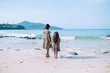 Little adorable girls ina leopard dress on white beach look at the sea. Family vacation. Back view