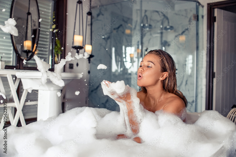 Fototapeta Concept of sensual water care and enjoyment at home. Full length portrait of beautiful brunette woman blowing foam while taking relaxing bath