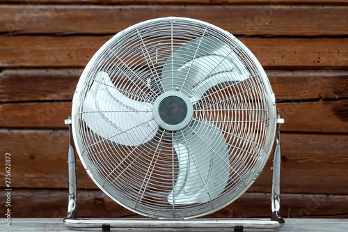 Fototapety, obrazy: Large tabletop ventilator on the table against the background of a wooden wall. The concept of heat, hot weather, air conditioning