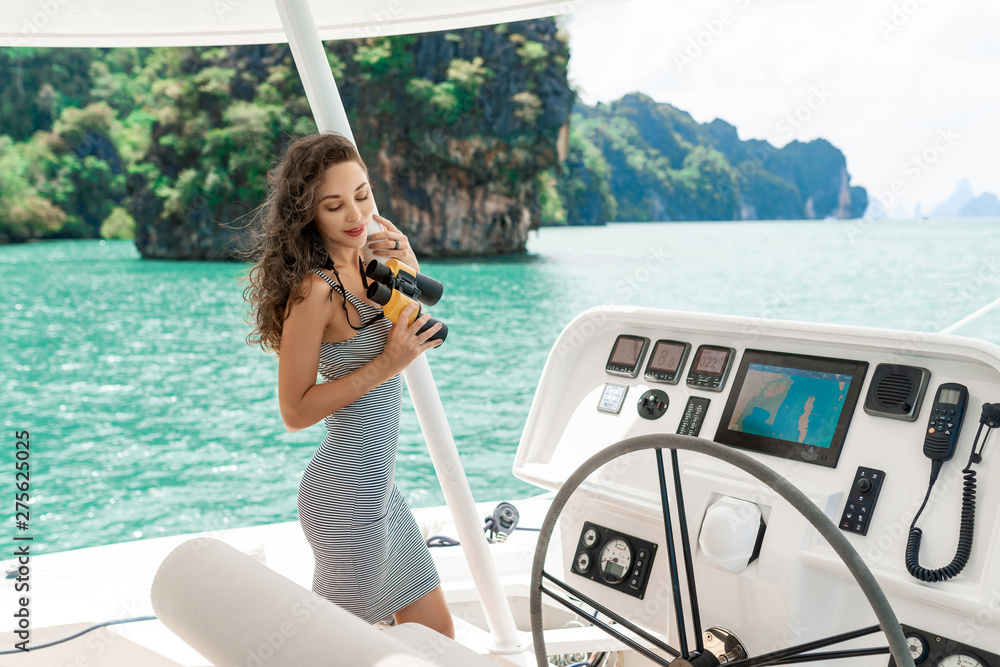 Fototapety, obrazy: Attractive and gorgeous brunette standing and driving on modern yacht. Adorable girl relaxing and posing at yacht. Model wearing striped dress and holding binoculars. Luxury summer vacation