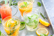 Assorted summer cold citrus drinks on a metal tray, horizontal