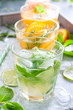 Mojito on the background of summer cold drinks with citrus fruits: lemonade, oranzhad, grape juice and mandarin juice, selective focus