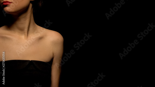 Photo  Woman in seductive black dress standing against black background, prostitution