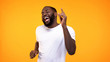 Happy relaxed black man dancing against yellow background, having fun on party