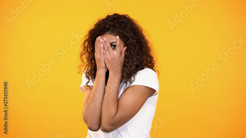 Obraz na plátne Frightened biracial woman watching horror movie, closing face with hands, fear