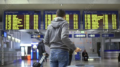 Man traveler looking at time table in train station, preparing for departure Billede på lærred