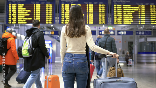 Fotografering  Girl looking at flight arrive and departure board, waiting for check-in, airport