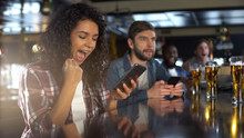 Cheerful Biracial Lady In Pub Celebrating Successful Bet On Sports, Online App
