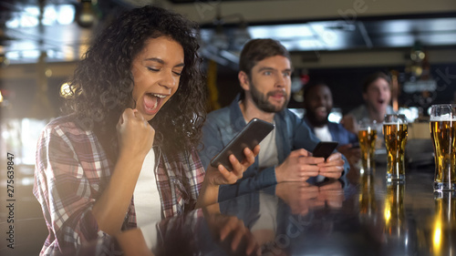 Photo Cheerful biracial lady in pub celebrating successful bet on sports, online app