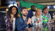 Brazilian soccer fans with flag cheering for national team, hoping for victory