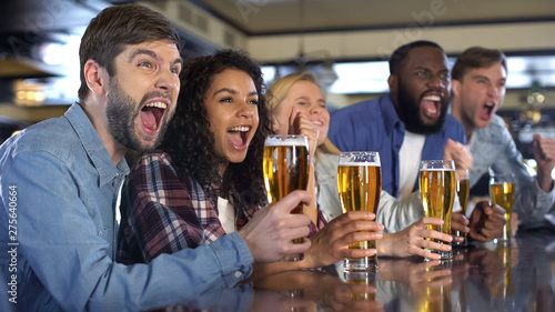 Foto  Emotional sport fans with beer glasses celebrating team victory in brewery pub