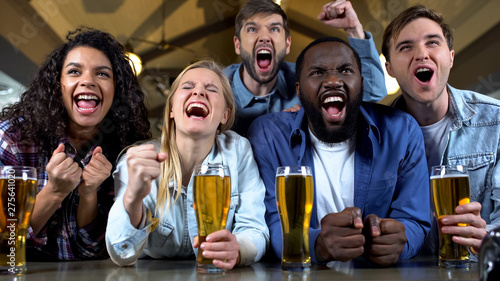 Foto  Young multi-racial friends rooting for favorite team, watching championship pub