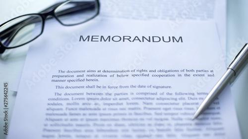 Obraz Memorandum lying on table, pen and eyeglasses on official document, business - fototapety do salonu