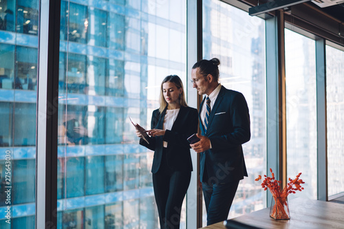 Fototapeta  Mature caucasian male and female company workers dressed in elegant suits checki