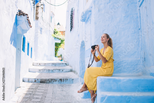 Positive hipster girl enjoying time for photographing beautiful city streets with chaouen exterior, cheerful woman feeling carefree during summer trip to Morocco for discover berber culture #275646863