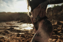 Beautiful Sexy Woman In Black Underwear. The Body Is Covered With Many Tattoos. Dreadlocks On The Head . Posing Against Sandy Career And Black Fabric.