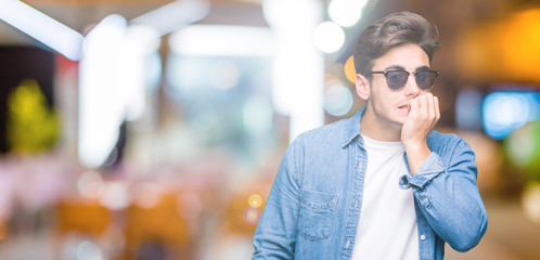 Young handsome man wearing sunglasses over isolated background looking stressed and nervous with hands on mouth biting nails. Anxiety problem.