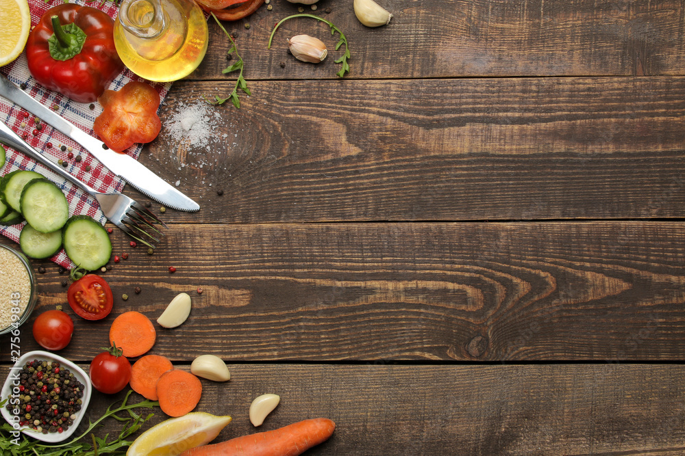 Fototapety, obrazy: Ingredients for cooking salad. Various vegetables and spices carrots, tomatoes, cucumbers, peppers and arugula on a brown wooden table. top view.