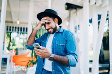 Amazed Hipster Blogger Dressed In Denim Apparel Shocked With Message About Low Charge Of Battery On Smartphone Gadget, Surprised Man In Stylish Denim Shirt Forget About Meeting Received Reminder News