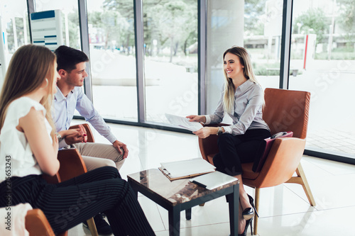 Fototapeta Financial advisor showing report to young couple for their investment. Salesman and positive couple talking about purchase. Happy couple consulting financial agent for loan. obraz