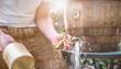 canvas print picture - bayerischer Mann in Lederhose sticht ein Holzfass Bier im Garten an und genießt den ersten Schluck